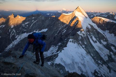 Verso il Tyndall, Dent d'Herens illuminata dai primi raggi di sole e l'ombra del Monte Bianco all'orizzonte.