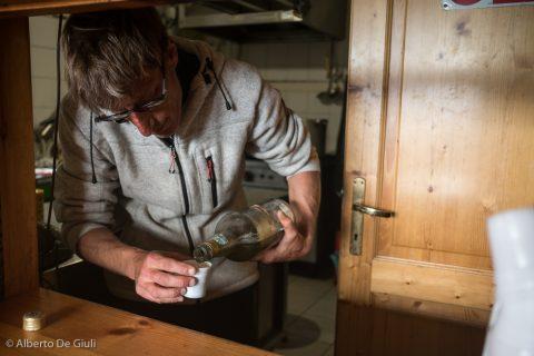 Diego serve il suo Genepi non solo al check-in, ma alla fine di ogni pasto e anche al check-out. Offre la casa, obbligatorio. Rifugio Aosta, settembre 2020.